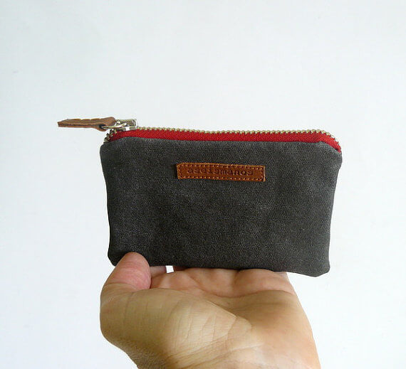 grey and red coin purse with hand