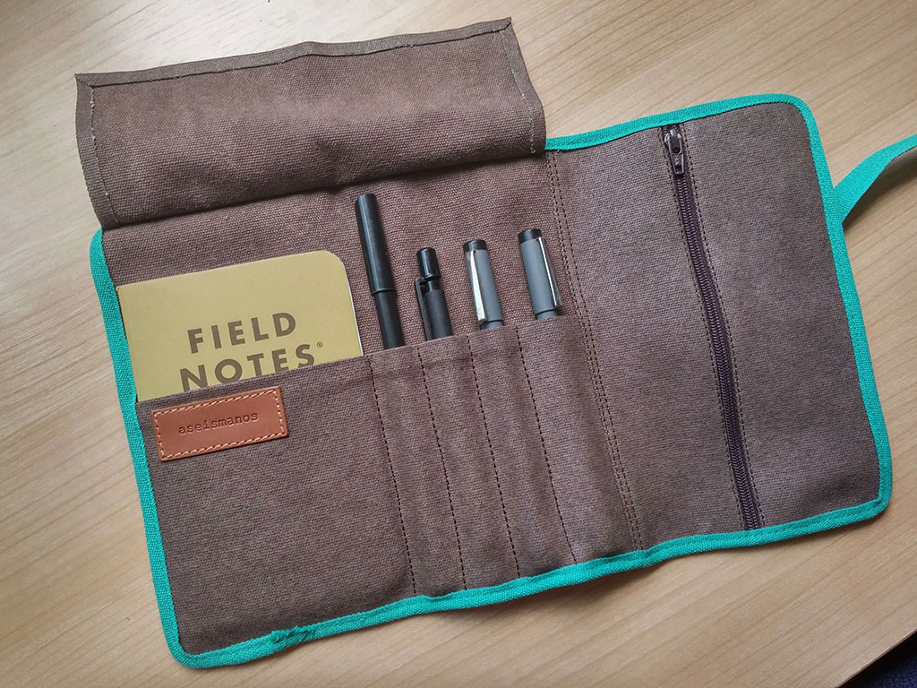 Pencil roll up case with journal and pens inside