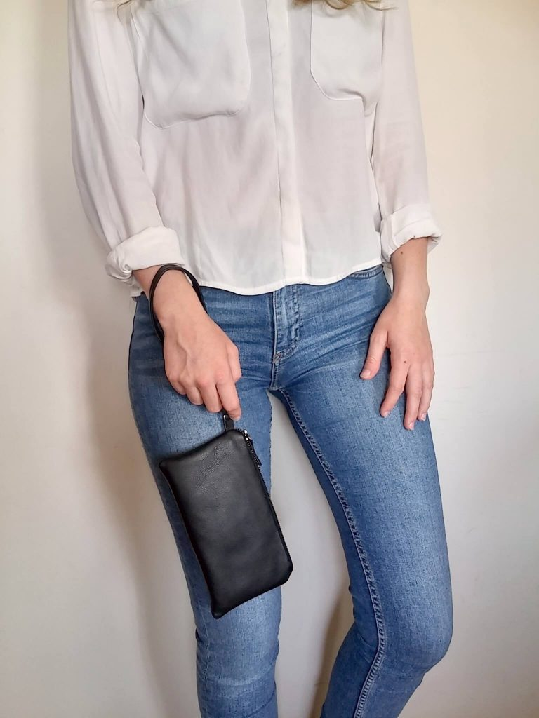 Black leather clutch with wristlet hanging along body