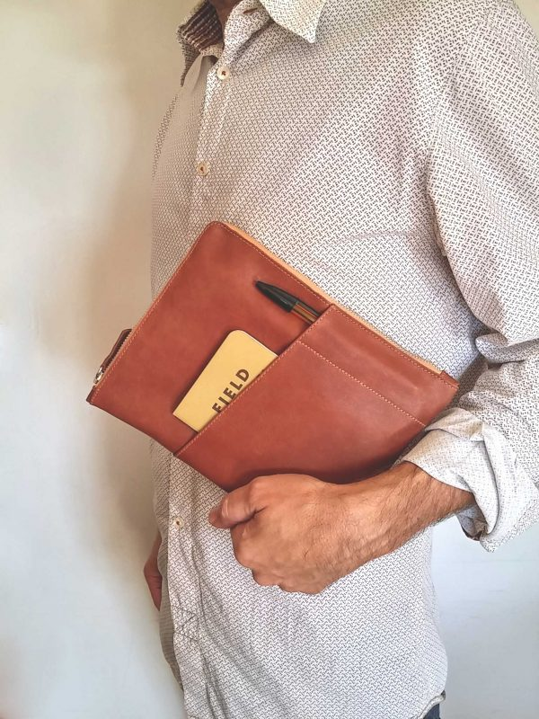 Leather planner sleeve held in hand