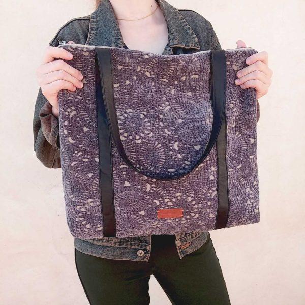 purple tapestry bag held in hands