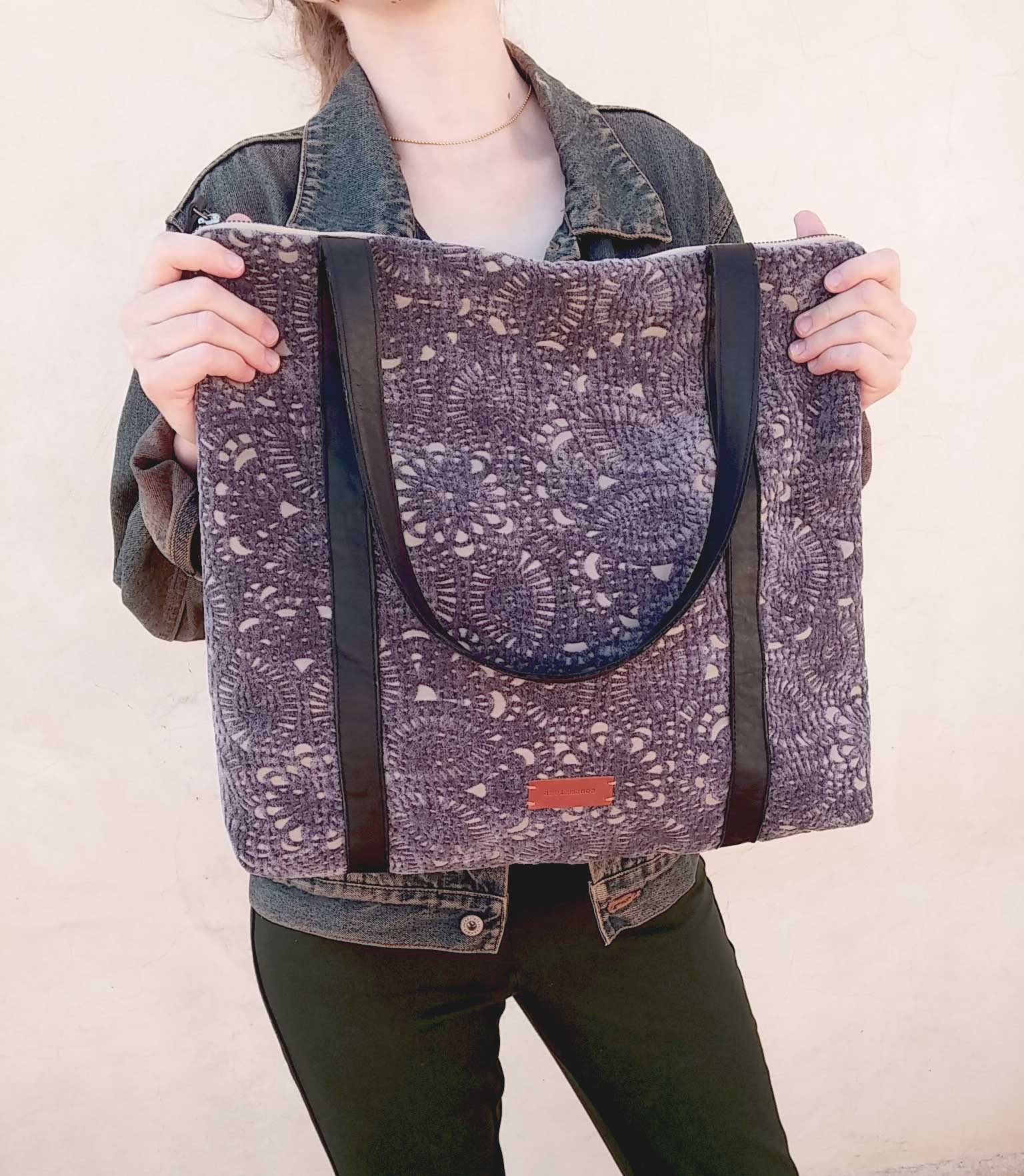 purple tapestry bag held in hands