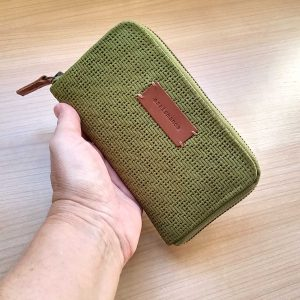 Medium moss leather wallet held in had