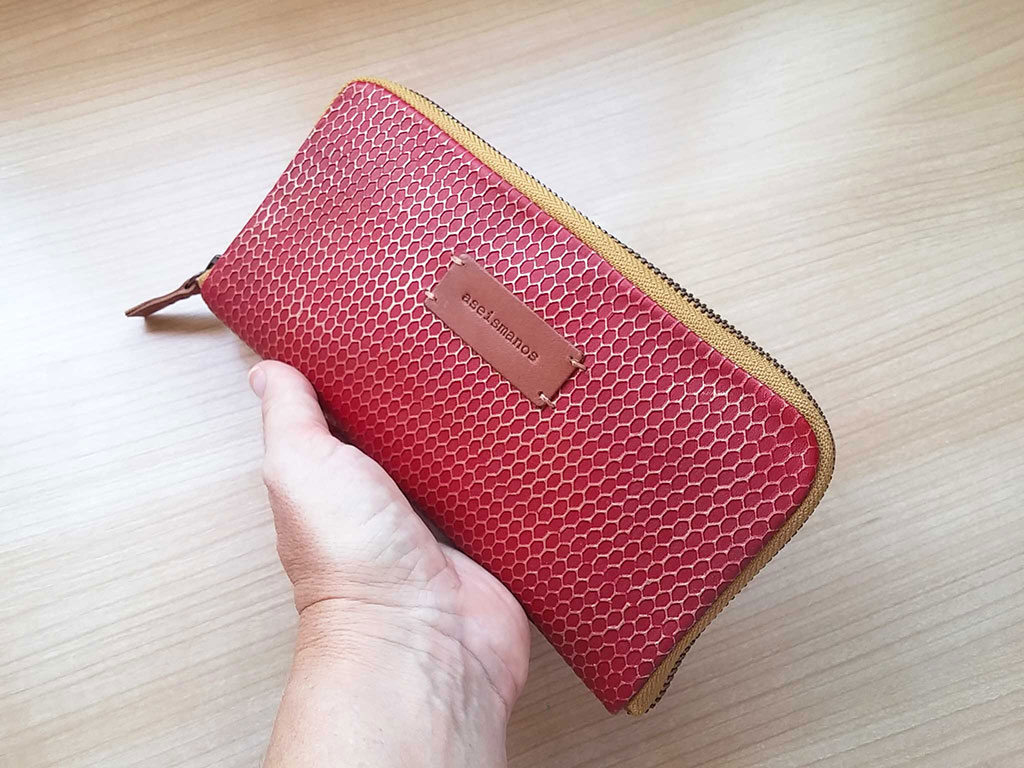 aseismanos red leather wallet held in hand